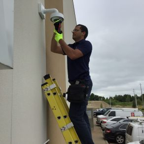 Electronic Security Technician on a ladder installing a video surveillance camera at an office building with vehicles in parking lot behind