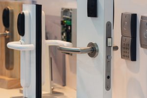 Close up shot of a white door with lever handles, a key pad, and swipe access control