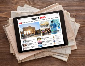 "Tablet on stack of newspapers, tablet screen reads ""Today's News"" and features a number of news articles with text and pictures. Articles are not official news stories, they are intended as graphic display."